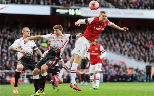 Per Mertesacker and Steven Gerrard both challenge for the ball as Martin Skrtel looks on the Gunners won the game 2-1