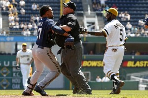 Brewers outfielder Carlos Gomez, left, tries to get past umpire Fieldin Culbreth (c.) to Pirates starting pitcher Gerrit Cole (not seen) in the third inning Sunday in Pittsburgh.