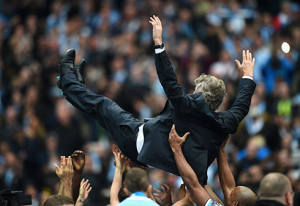 Man City manager Manuel Pellegrini gets the bumps from his players after their BPL title win