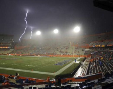 Lightning strikes near Ben Hill Griffin Stadium at Florida Field during a weather delay before an NCAA college football game between Florida and Idaho in Gainesville.